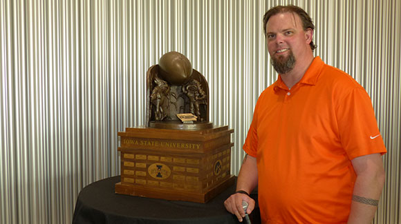man with cy-hawk trophy